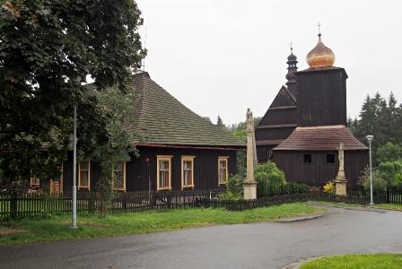 Kostel s farou a zvonicí.